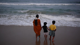 A family plays with the waves on Marina beach,Chennai,India Footage