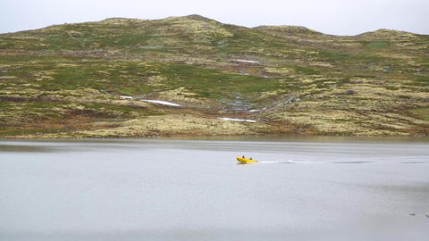 Yellow motor boat floats on a lake in Norway Live Action
