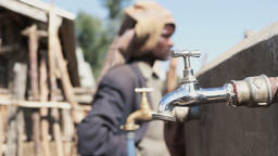 People near tap with water GIF