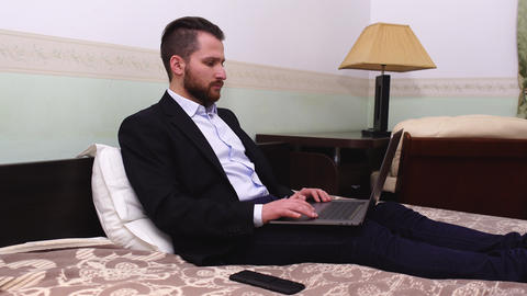 Handsome businessman in suit sitting in bed with laptop. Handsome bearded man Live Action