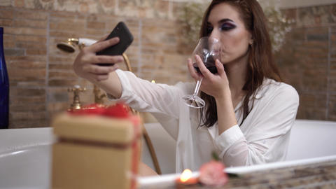 Young woman with bright makeup making selfie sitting in the bath and drinkin red Footage
