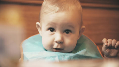 Funny baby girl wearing bib ready for meal, close-up Live Action