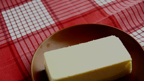 Brown plate with a piece of classic new York cheesecake, spinning on a red Live Action