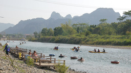 Tourists relax at the river while canoes pass,Vang Vieng,Laos Footage