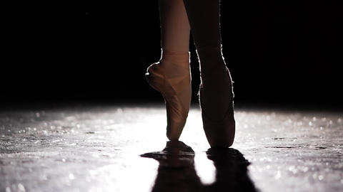 Silhouette of a ballerina standing standing on her pointe ballet shoes in Live Action