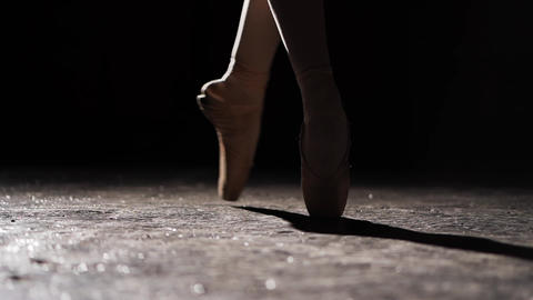 Female legs in pointe shoes. Ballet practice. Beautiful slim graceful legs of Live Action