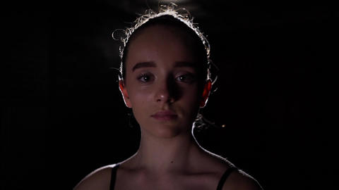 Portrait of young beautiful girl in dark with strong lamp light in the back Footage