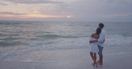 Honeymoon couple relaxing on beach looking at sunset embracing in love Live Action
