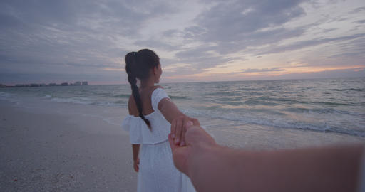 Young couple holding hands woman leading boyfriends walking towards beach sunset Footage