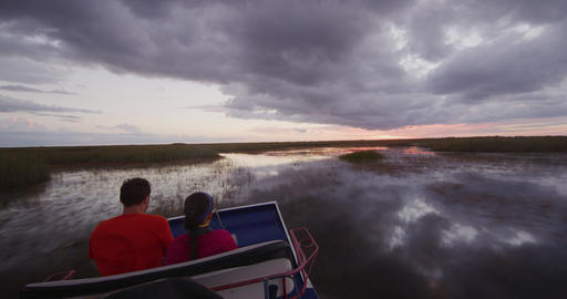 Airboat in Everglades in Florida - tourists on tour at sunset Live Action