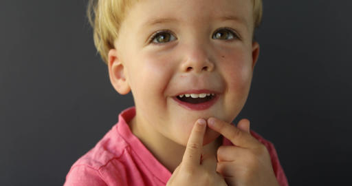 Boy points his fingers of both hands on his teeth ビデオ