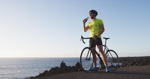Energy sports drink - cyclist drinking from water bottle on rode bike training Footage