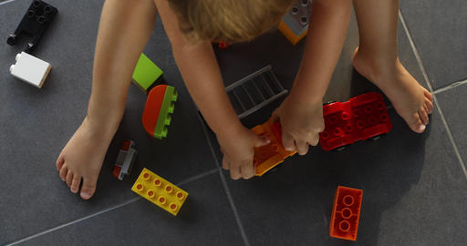 Child playing with lots of colorful plastic blocks indoor Footage