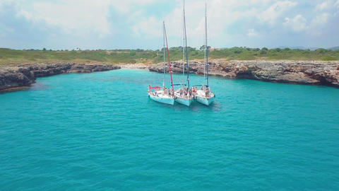 Top view of the sailing boats in blue lagoon. Swimmers enjoying in clear blue Live Action