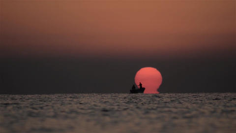 Fishermen spread their nets at sea when a round sun and red out of wate 01 Footage
