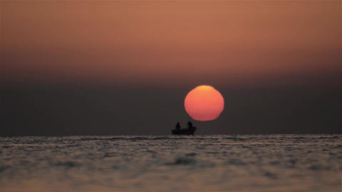 Fishermen spread their nets at sea when a round sun and red out of wate 02 Footage