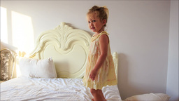 Little Girl Claps Hands Jumps down Bed to Pillows on Floor Footage