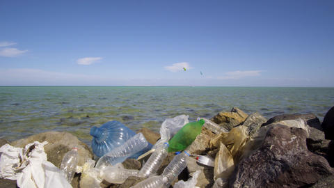 Dirty plastic bottles on the stone beach. Environmental pollution Live Action
