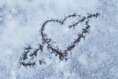 Valentine's day. Heart pierced by an arrow drawn on snow Photo