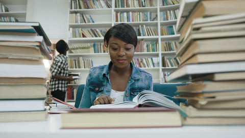 Smiling african female student studying, reading book in the modern library Live Action