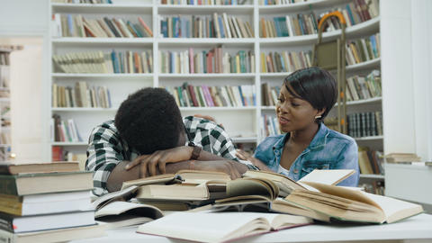Tired african young man sleeping on the books while african young woman waking Live Action