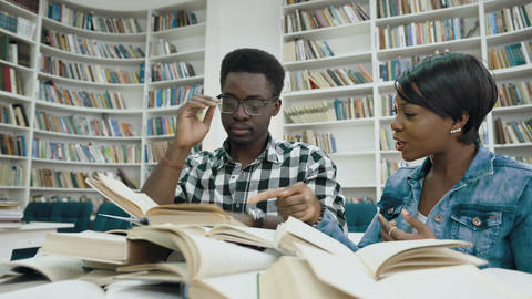 African female student reading book while tired african male student sleeping on Footage