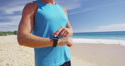 Sports smartwatch - Athlete runner checking cardio on fitness smartwatch running Live Action
