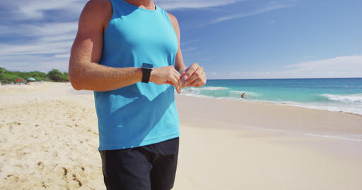 Athlete runner checking cardio on sports smartwatch jogging on beach outdoor Live Action