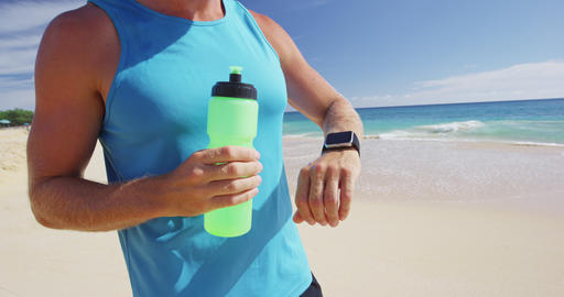 Sports smartwatch - Athlete runner drinking water or energy sports drink bottle Footage