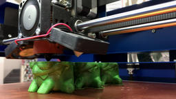 Working 3D Printer Printing Toys from Green Plastic with Additive Technology Footage