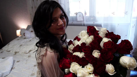 Beautiful girl sitting with a big bouquet of flowers, joy and smile, slow motion Footage