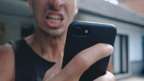 Angry Man Using Smartphone. Furious yelling man with smartphone in hand Footage