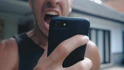 Angry Man Using Smartphone. Furious yelling man with… Stock Video Footage