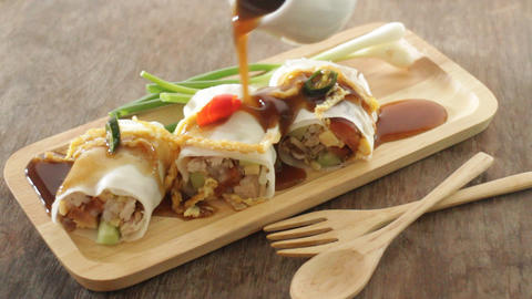 Serving spring rolls with vegetables on wooden plate Footage