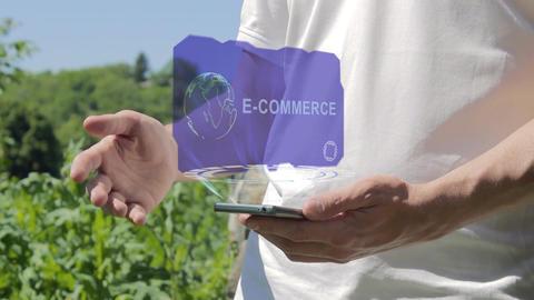 Man shows concept hologram E-commerce on his phone Live Action