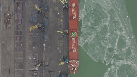 Aerial 4k UHD footage Cargo freight ship with working crane bridge in shipyard Footage