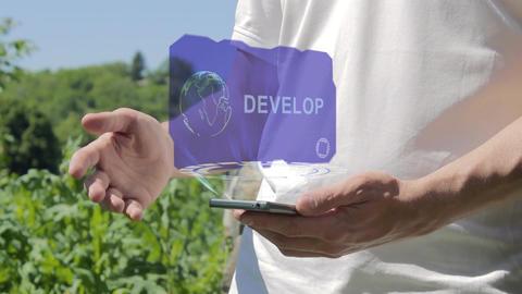Man shows concept hologram Develop on his phone Live Action