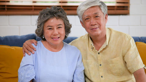 Asian senior couple of a loving looking at camera smiling sitting on sofa at Live Action