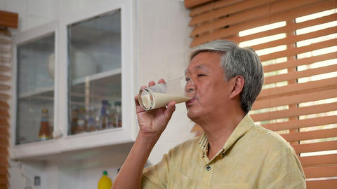 Portrait senior asian man drinking milk in kitchen at home Footage