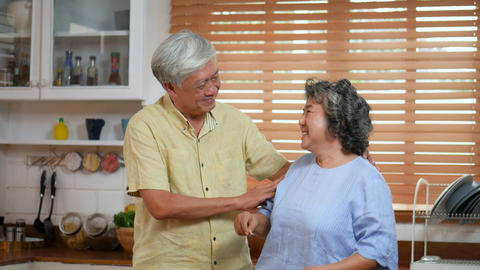 Asian senior couple dancing cooking in kitchen at home Live Action