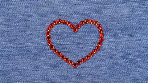 Rotation of the heart laid out of red rhinestones, romantic background with copy Footage