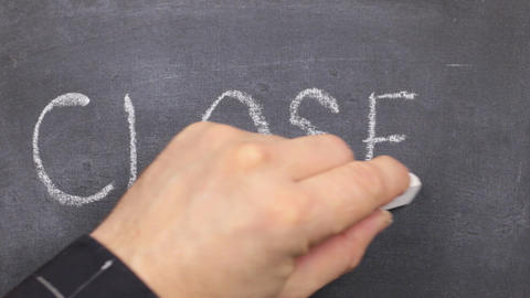 Small blackboard with the word closed, written on it in chalk Footage