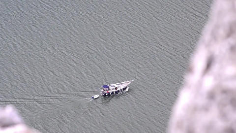 Blue boat that goes after her rescue boat is seen on some rocks above the river Footage