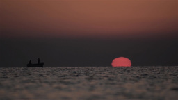 Fishermen spread their nets at sea when a round sun and red out of wate 03 Footage