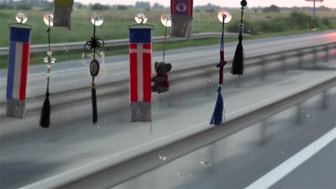 Flags and other ornaments hanging from the windshield of a lorry on a road he Footage