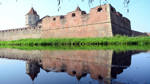 Fortress walls which are reflected in the water in the moat that surrounds them Footage