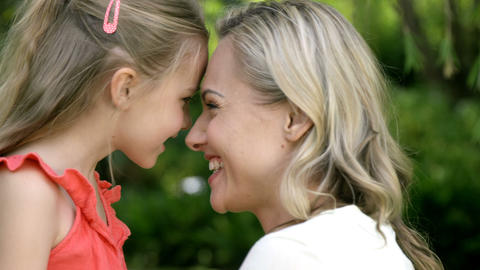 Portrait of cute mother and daughter embracing and smiling Live Action