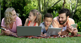 Portrait of cute family are lying on the grass and using electronic devices Footage