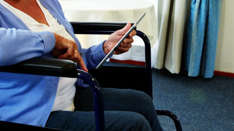 Retired person in wheel chair using tablet computer Live Action
