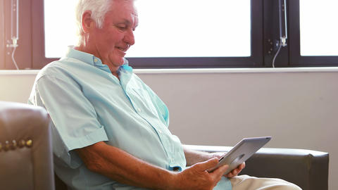 A senior man having a video conference with tablet pc Live Action